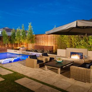 """Esempio di una piscina moderna a """"L"""" di medie dimensioni e dietro casa con fontane e pedane"""