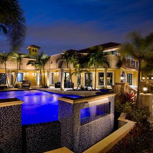 Ejemplo de piscina infinita, actual, extra grande, rectangular, en patio, con adoquines de piedra natural