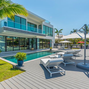 Inspiration for a contemporary rectangular lap pool in Miami with a hot tub and decking.