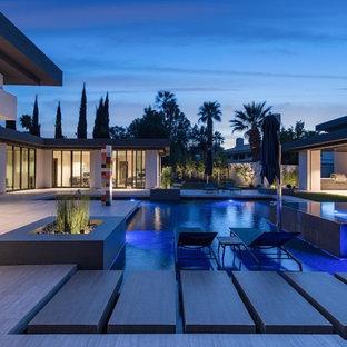 Esempio di una grande piscina monocorsia moderna personalizzata dietro casa con piastrelle e una vasca idromassaggio