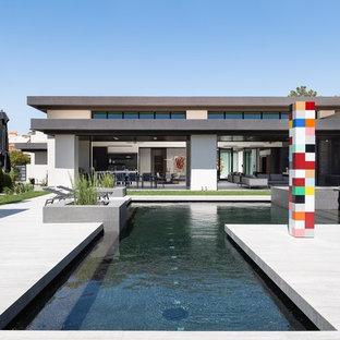 Large minimalist backyard tile and custom-shaped lap hot tub photo in Las Vegas
