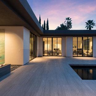Immagine di una grande piscina monocorsia minimalista personalizzata dietro casa con piastrelle e una vasca idromassaggio