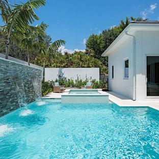 Mittelgroßer Moderner Pool hinter dem Haus in rechteckiger Form mit Wasserspiel und Natursteinplatten in Miami
