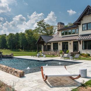 """Idee per una grande piscina classica a """"L"""" dietro casa con fontane e pavimentazioni in cemento"""