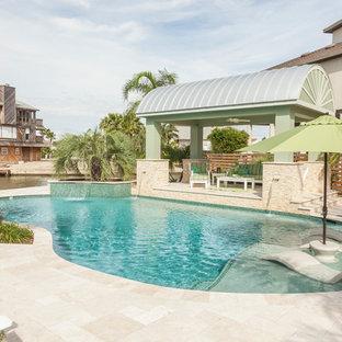 ヒューストンの中サイズのオーダーメイドトロピカルスタイルのおしゃれなプール (タイル敷き) の写真