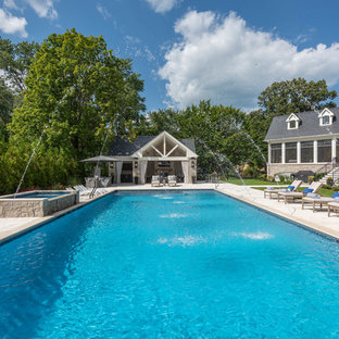 Expansive traditional backyard rectangular pool in Chicago with a pool house and natural stone pavers.