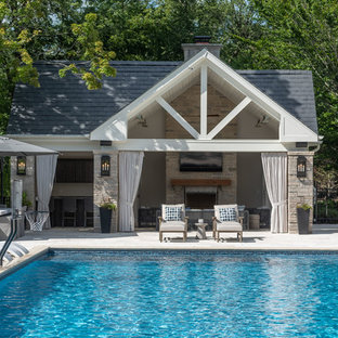 Design ideas for an expansive traditional back rectangular swimming pool in Chicago with a pool house and natural stone paving.