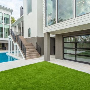 Foto de piscina minimalista, grande, en forma de L, en patio trasero, con privacidad y adoquines de hormigón
