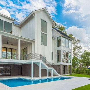 Imagen de piscina minimalista, grande, en forma de L, en patio trasero, con privacidad y adoquines de hormigón