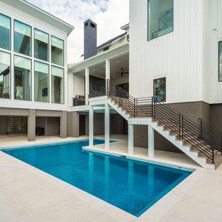 Diseño de piscina minimalista, grande, en forma de L, en patio trasero, con privacidad y adoquines de hormigón