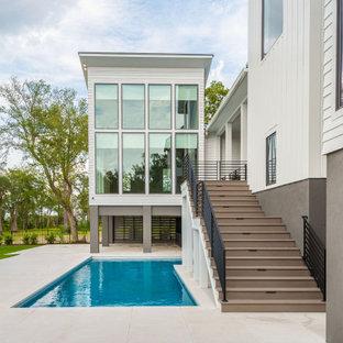 Diseño de piscina moderna, grande, en forma de L, en patio trasero, con privacidad y adoquines de hormigón