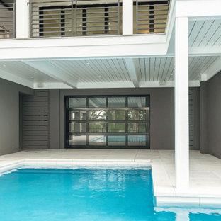 Ejemplo de piscina moderna, grande, en forma de L, en patio trasero, con privacidad y adoquines de hormigón