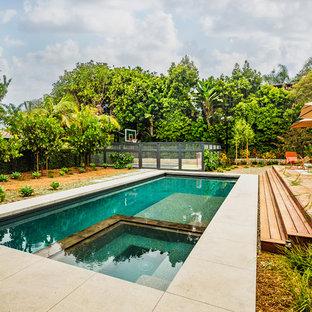 Imagen de piscinas y jacuzzis alargados, retro, de tamaño medio, rectangulares, en patio trasero, con losas de hormigón
