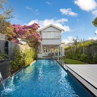 Photo of a small contemporary backyard rectangular lap pool in Sydney with a water feature and decking.