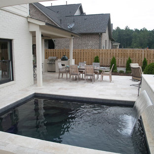 This is an example of a small backyard rectangular pool in Birmingham with natural stone pavers.