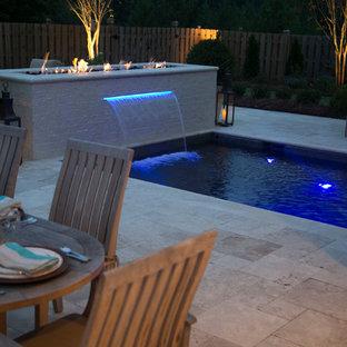 Foto de piscina pequeña, rectangular, en patio trasero, con adoquines de piedra natural