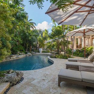 Imagen de piscina exótica, grande, tipo riñón, en patio lateral, con adoquines de piedra natural