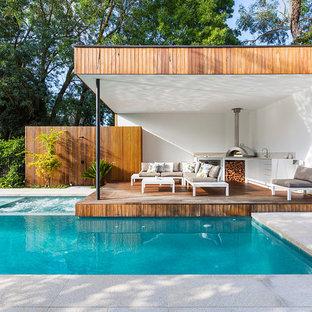 """Esempio di una piscina monocorsia contemporanea a """"L"""" dietro casa con una vasca idromassaggio e pavimentazioni in cemento"""