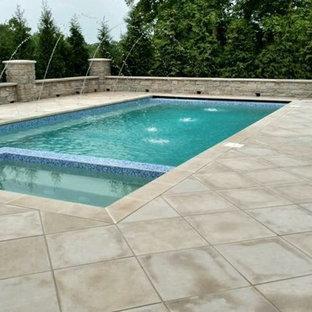 Imagen de piscinas y jacuzzis alargados, modernos, de tamaño medio, rectangulares, en patio trasero, con losas de hormigón