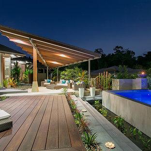 Foto de piscina con fuente elevada, exótica, de tamaño medio, rectangular, en patio delantero