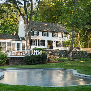 Modelo de piscina de estilo de casa de campo, tipo riñón, en patio trasero, con adoquines de piedra natural