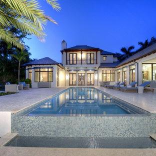Diseño de piscina infinita, exótica, extra grande, rectangular, en patio trasero, con suelo de baldosas