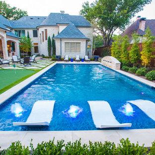 Mittelgroßes Mediterranes Sportbecken hinter dem Haus in rechteckiger Form mit Wasserspiel und Betonplatten in Dallas