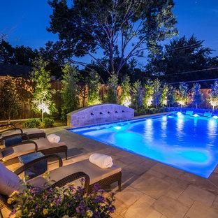 Immagine di una piscina monocorsia mediterranea rettangolare di medie dimensioni e dietro casa con pavimentazioni in pietra naturale e fontane