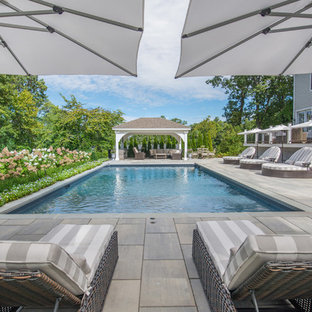 Example of a classic backyard tile and rectangular pool design in New York
