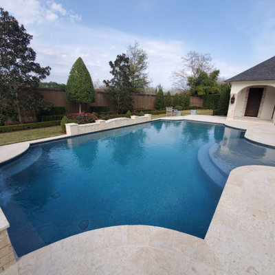 Example of a mid-sized tuscan backyard tile and custom-shaped lap pool fountain design in Houston