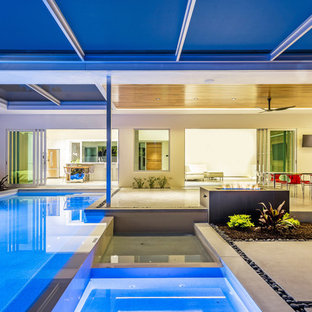 Inspiration for a large contemporary backyard concrete and rectangular infinity hot tub remodel in Tampa