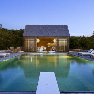Immagine di una piscina a sfioro infinito stile marinaro rettangolare di medie dimensioni e dietro casa con una dépendance a bordo piscina e pedane
