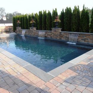 Modelo de piscina con fuente natural, tradicional, rectangular, en patio trasero, con adoquines de ladrillo