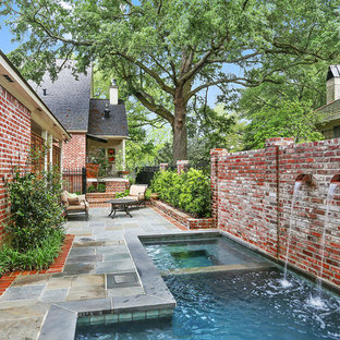 Inspiration for a small transitional courtyard custom-shaped natural pool in New Orleans with a hot tub and natural stone pavers.