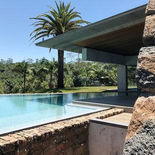 Imagen de piscina infinita, grande, en forma de L, en patio lateral, con adoquines de piedra natural