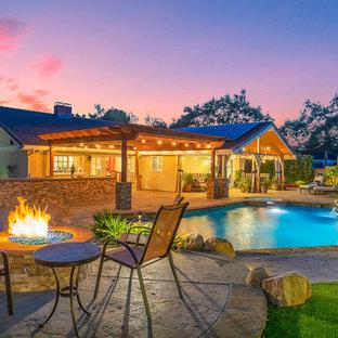 Ejemplo de piscinas y jacuzzis naturales, clásicos, grandes, a medida, en patio trasero, con losas de hormigón