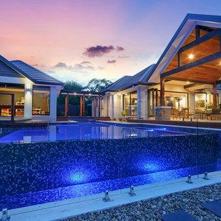 Ejemplo de piscina elevada, exótica, grande, rectangular, en patio trasero