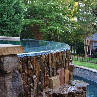 Imagen de piscina con fuente infinita, retro, de tamaño medio, a medida, en patio trasero, con suelo de baldosas