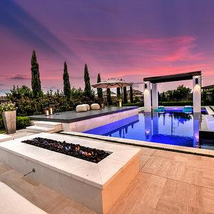 Ejemplo de piscinas y jacuzzis alargados, actuales, grandes, rectangulares, en patio trasero, con suelo de baldosas