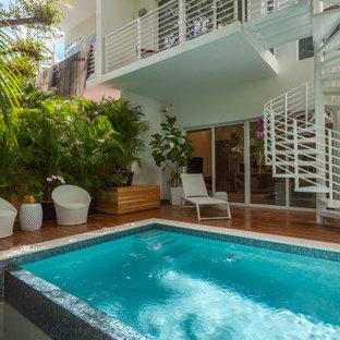Esempio di una piscina design rettangolare dietro casa con pedane