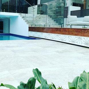 Imagen de piscina asiática, grande, en forma de L, en patio trasero, con adoquines de piedra natural