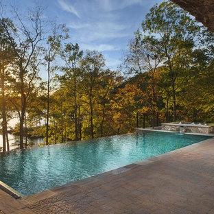 Modelo de piscinas y jacuzzis infinitos, exóticos, de tamaño medio, rectangulares, en patio trasero, con adoquines de hormigón