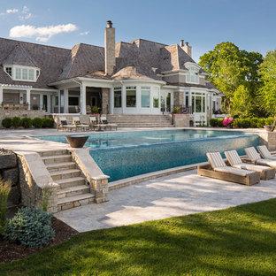 Esempio di una grande piscina a sfioro infinito stile marino rettangolare dietro casa con pavimentazioni in pietra naturale