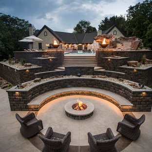 Imagen de piscina con tobogán alargada, clásica renovada, grande, rectangular, en patio trasero, con adoquines de hormigón