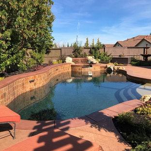 Imagen de piscinas y jacuzzis de estilo americano, de tamaño medio, a medida, en patio trasero, con suelo de hormigón estampado