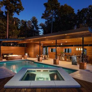 Ejemplo de casa de la piscina y piscina moderna, grande, rectangular, en patio trasero, con suelo de hormigón estampado