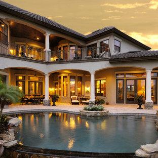 Großer Mediterraner Schwimmteich hinter dem Haus in Nierenform mit Wasserspiel und Natursteinplatten in Tampa