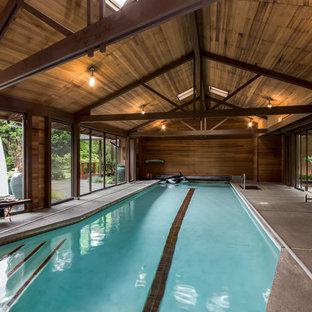 Ejemplo de casa de la piscina y piscina alargada, de estilo zen, extra grande, rectangular, en patio trasero, con losas de hormigón