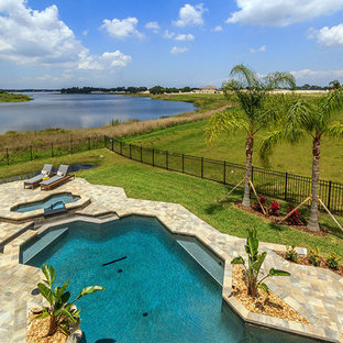 Example of a large classic backyard stone and custom-shaped pool design in Orlando