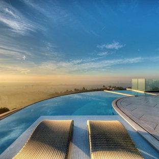 """Ispirazione per una grande piscina a sfioro infinito design a """"C"""" dietro casa con una vasca idromassaggio e piastrelle"""